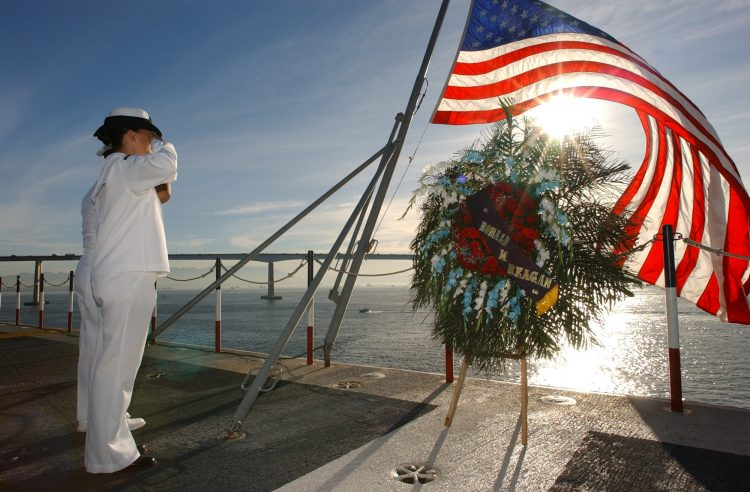 U.S. Navy cadets salute the U.S. flag in a ceremony on board of USS Ronald Reagan in Rio de Janeiro. (Photo: AP photo)